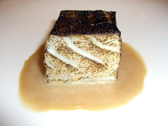 Taco de bacalao asado bajo la llama, servido con una sopa rústica de pan sopako