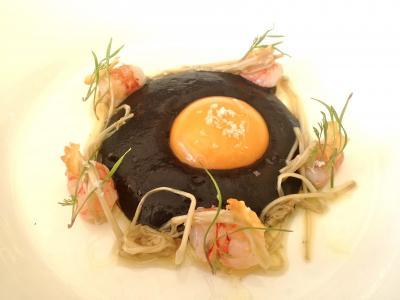 Huevo negro con angulas vegetales y gambas al ajillo.