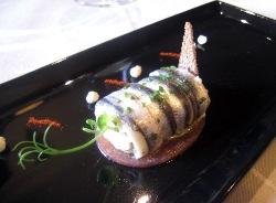 Lomitos de anchoa, apenas marinados, dispuestos como un rulo relleno de un cremo