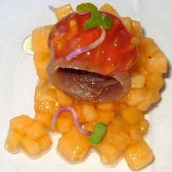 Melón cantalup, anchoa, tomate y brotes picantes de rábano