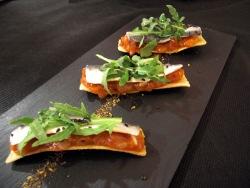 Tosta de sardina marinada con tomate, rúcula y sésamo