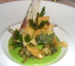 Ancas de rana salteadas sobre una crema de ajos confitados teñida de verde por e