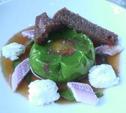 Yema de huevo poché envuelta en gelatina de pimiento verde con tiras de piquillo