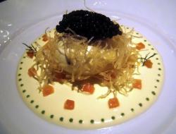Huevo escalfado coronado con caviar y una juliana de pasta brick sobre crema agr