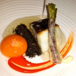 Bacalao confitado con calcot en tempura y jugo de ajo negro
